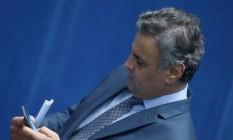 O senador Aécio Neves recebeu a notícia por celular, no plenário do Senado Foto: Jorge William | Agência O Globo