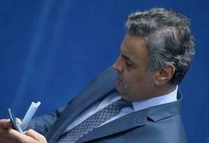 O senador Aécio Neves recebeu a notícia por celular, no plenário do Senado Foto: Jorge William   Agência O Globo