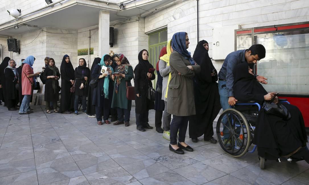 Iranianos fazem fila em um sessão eleitoral para votar nos candidatos presidenciais e municipais, em Teerã. Os eleitores se pronunciarão entre a manutenção da política de abertura promovida por Rouhani e o nacionalismo defendido por Raisi Vahid Salemi / AP