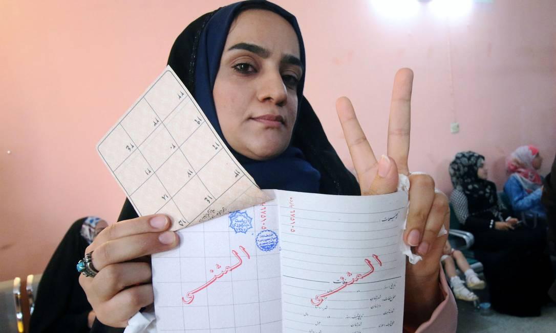 Uma mulher posa para foto após votar nas eleições presidenciais iranianas na embaixada do país na cidade iraquiana de Basra HAIDAR MOHAMMED ALI / AFP