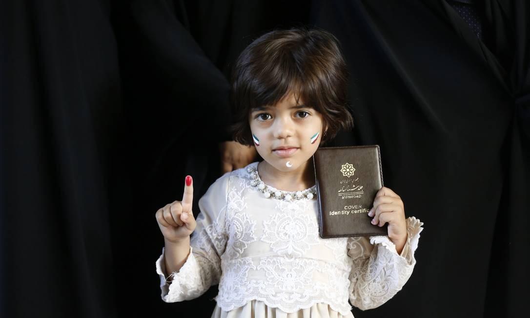 Uma menina iraniana mostra seu dedo pintado e a identidade de sua mãe depois de ter votado nas eleições presidenciais em um sessão eleitoral em Teerã ATTA KENARE / AFP