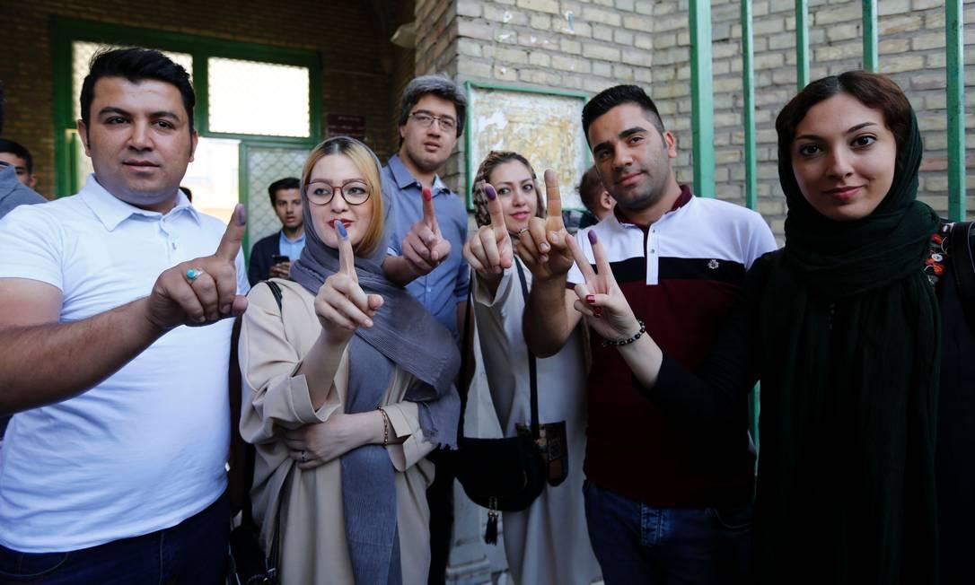 Iranianos mostram seus dedos pintados após votar nas eleições presidenciais em uma sessão eleitoral em Teerã. Muitos eleitores tinham dúvidas em quem votar. Enquanto alguns diziam que iriam boicotar a eleição, outros queriam votar para expressar sua raiva sobre a economia combalida ATTA KENARE / AFP