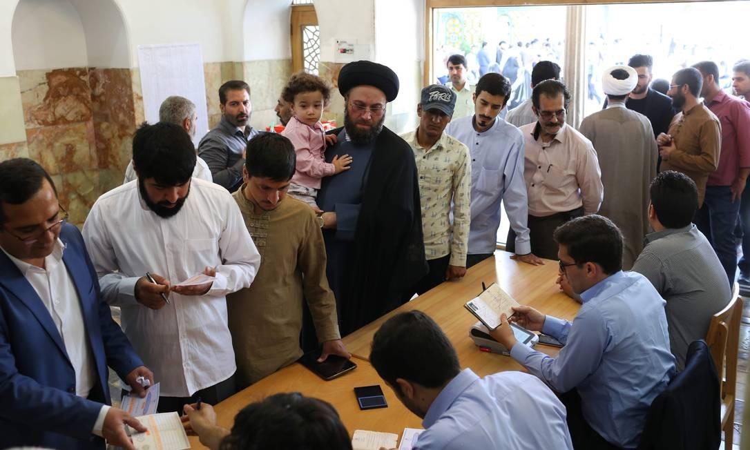 Homens chegam para votar na cidade de Qom, 130km ao Sul de Teerã. O atual presidente do país, Hassan Rouhani, tenta a reeleição após o acordo nuclear com as potências mundiais em 2015 que diminuiu o programa nuclear do país ALI SHAIGAN / AFP