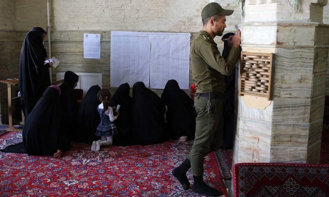 Iranianos checam uma lista antes de votar nas eleições presidenciais e municipais, na cidade de Qom. As seções eleitorais abriram às 3h30 GMT (0h30 Brasília) para 56,4 milhões de eleitores habilitados ALI SHAIGAN / AFP