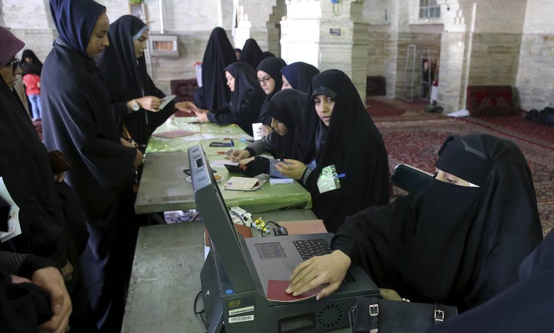 Eleitores esperam para pegar as cédulas nas eleições presidenciais e municipais em uma sessão eleitoral na cidade de Qom, ao Sul da capital de Teerã Ebrahim Noroozi / AP