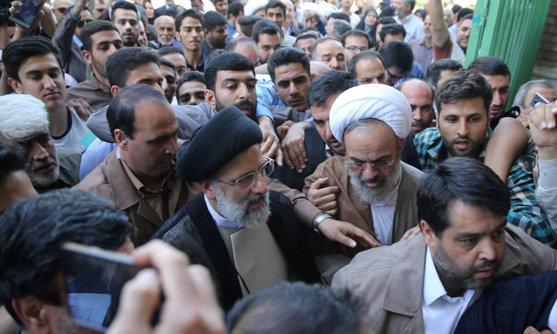 O candidato à Presidência do Irã Ebrahim Raisi chega para votar em Teerã com centenas de apoiadores. Raisi é o concorrente mais forte da ala conservadora e o principal rival de Hassan Rouhani, atual presidente do país TIMA AGENCY / REUTERS