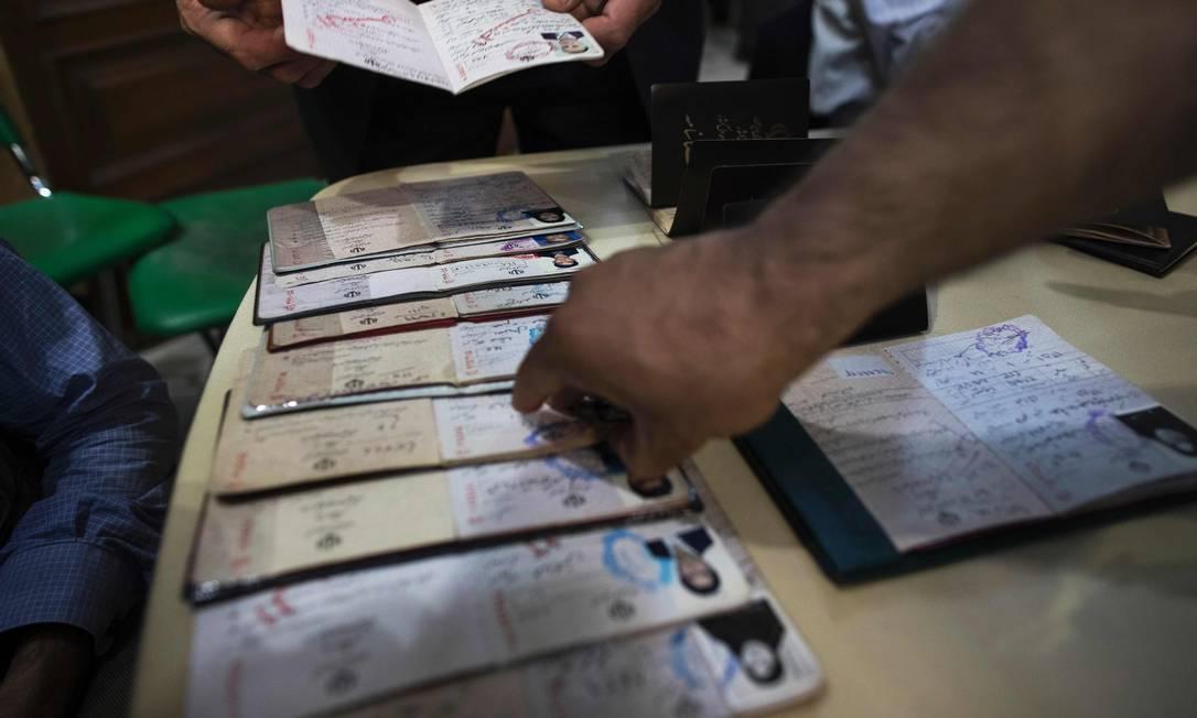 Um funcionário das eleições iranianas checa as identidades dos eleitores em uma sessão eleitoral em Teerã BEHROUZ MEHRI / AFP
