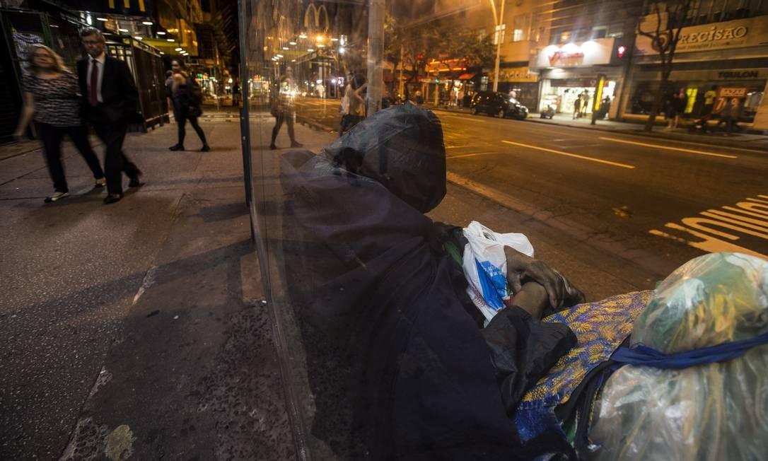 Ainda no bairro, uma mulher dorme sentada em um ponto de ônibus da Avenida Nossa Senhora de Copacabana Alexandre Cassiano / Agência O Globo