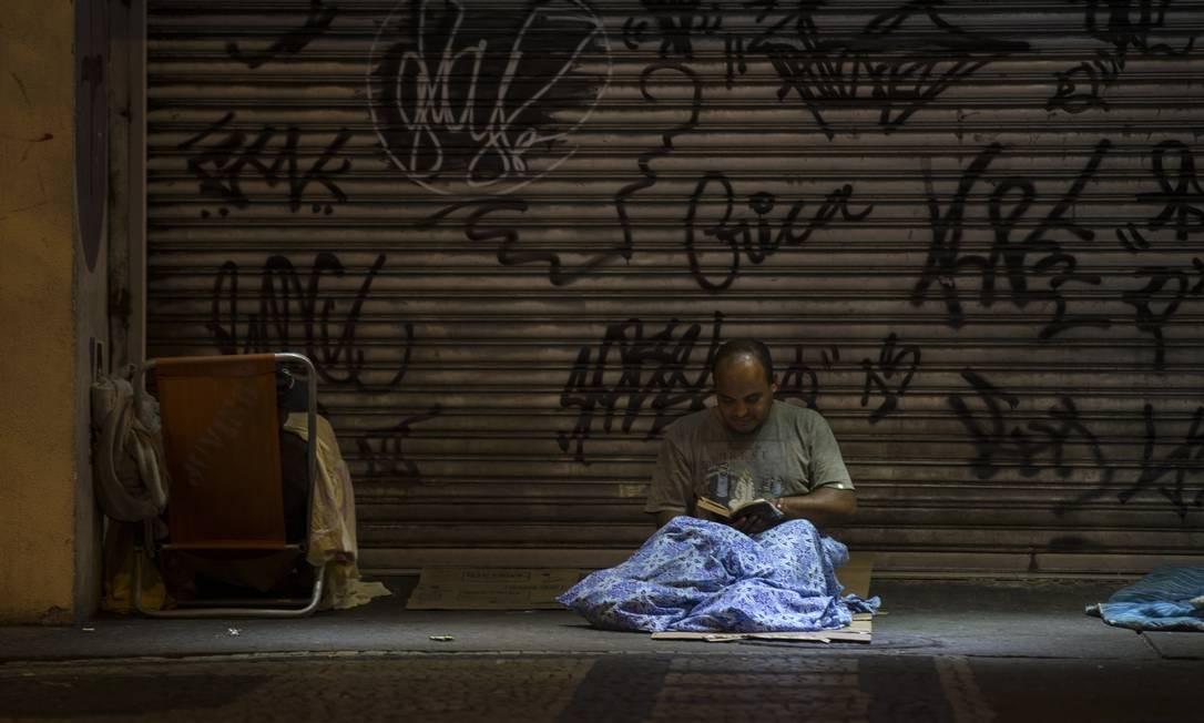 Em Copacabana, morador lê um livro na calçada em que passa as noites. Bairro é o segundo do Rio com maior quantidade de pessoas em situação de rua Alexandre Cassiano / Agência O Globo