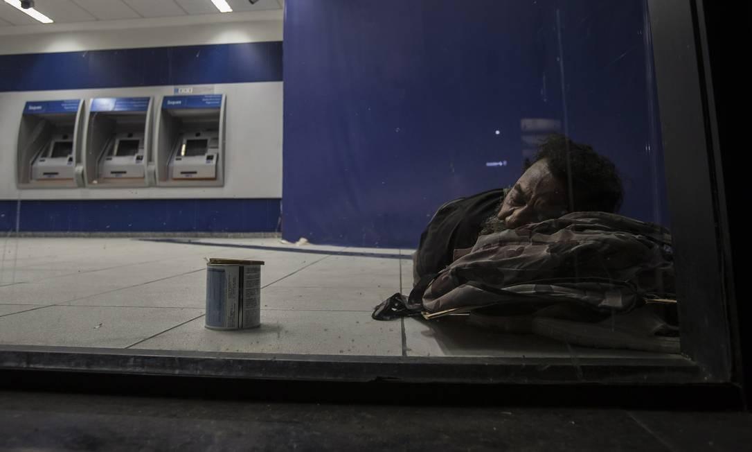 Outro homem dorme dentro do banco, próximo aos caixas eletrônicos Alexandre Cassiano / Agência O Globo