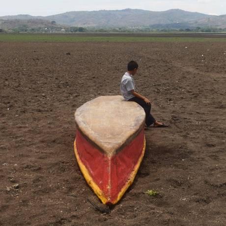 Garoto senta em um barco abandonado em região onde ficava o lago Atescatempa, na Guatemala, que desapareceu após um longo período de estiagem Foto: Marvin RECINOS/AFP