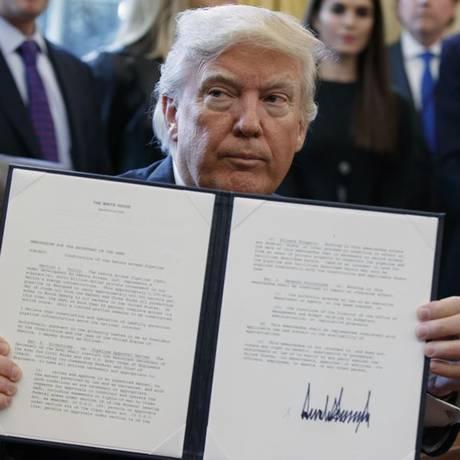 Trump mostra sua assinatura em ordem executiva que dá sinal verde à construção de gasoduto Foto: AP