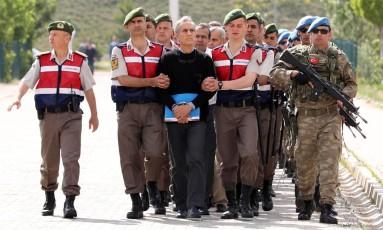 A polícia turca escolta o ex-comandante da Força Aérea Akin Ozturk para o julgamento do seu suposto envolvimento com a tentativa de golpe de Estado, em Ancara Foto: ADEM ALTAN / AFP