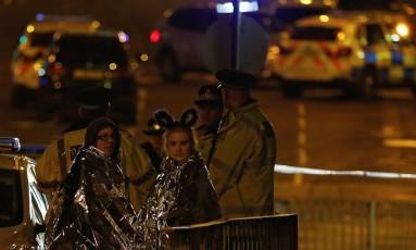 Jovens recebem ajuda de policiais após ataque Foto: ANDREW YATES / REUTERS