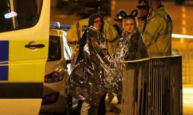 Mulheres se enrolam em cobertores térmicos enquanto recebem atendimento após atentado a show de Ariana Grande em Manchester, no Reino Unido Foto: ANDREW YATES / REUTERS