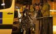 Mulheres se enrolam em cobertores térmicos enquanto recebem atendimento após atentado a show de Ariana Grande em Manchester, no Reino Unido