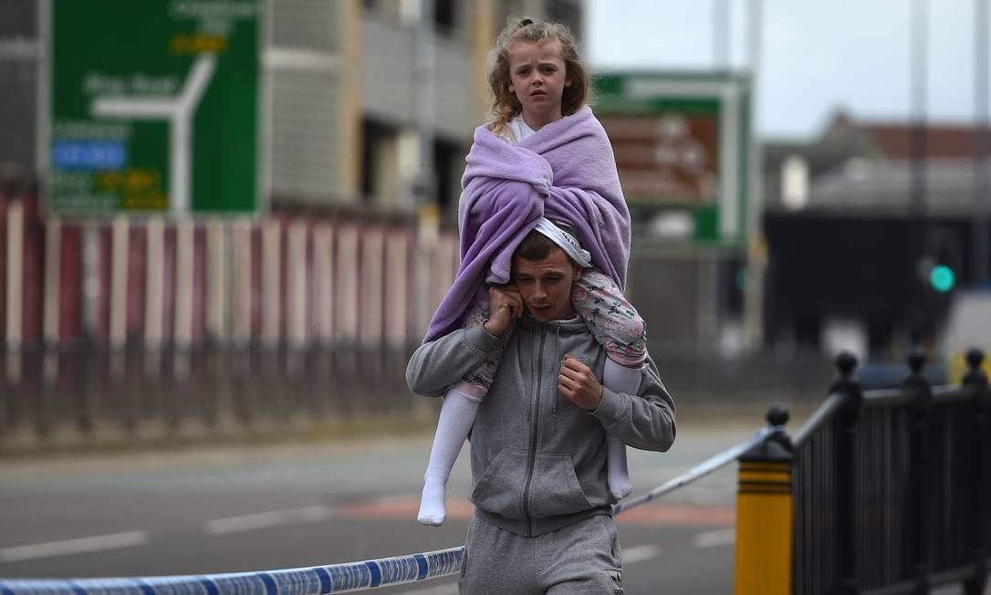 Homem carrega criança perto da estação Victoria, próxima à Arena Manchester OLI SCARFF / AFP