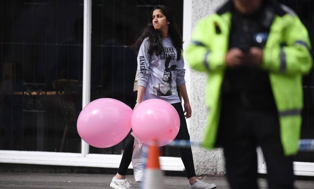 Menina vestindo camisa com foto de Ariana Grande deixa hotel em Manchester nesta terça-feira OLI SCARFF / AFP