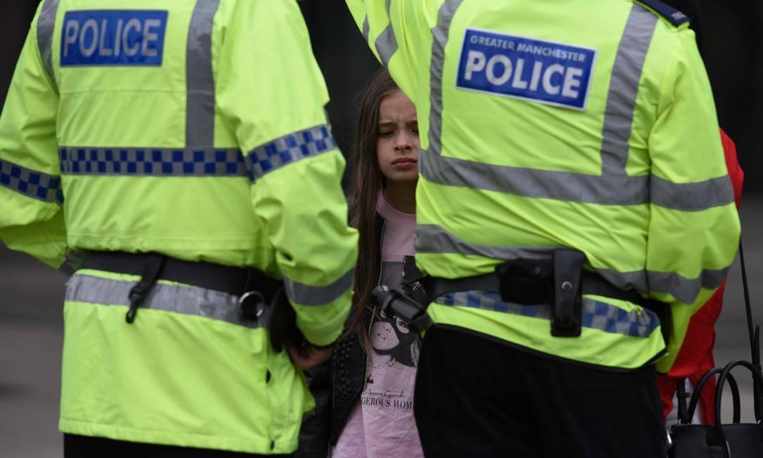 Mulher acompanhada de criança conversa com policiais em Manchester Foto: OLI SCARFF / AFP