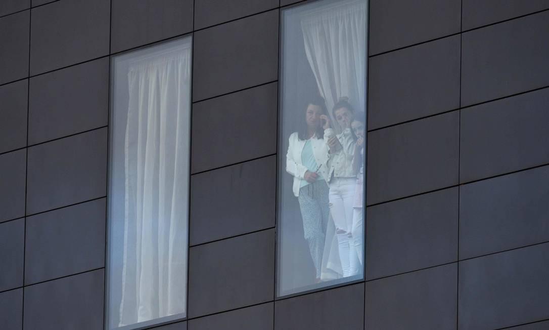 Sobreviventes do ataque observam as ruas a partir de hotel em Manchester Foto: OLI SCARFF / AFP