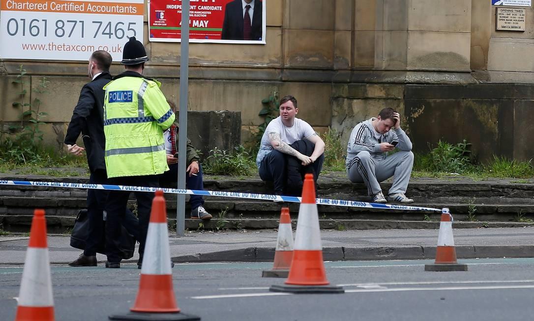 Pessoas sentam ao lado de área cercada pela polícia em Manchester ANDREW YATES / REUTERS