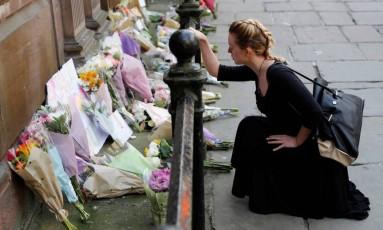 Mulher deixa flores em homenagem a vítimas de ataque terrorista após show de Ariana Grande em Manchester Foto: DARREN STAPLES / REUTERS