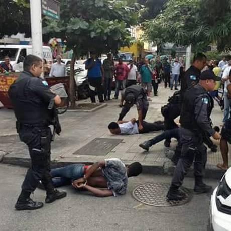 Quatro presos que estavam no carro roubado são algemados na rua Foto: Reprodução Facebook