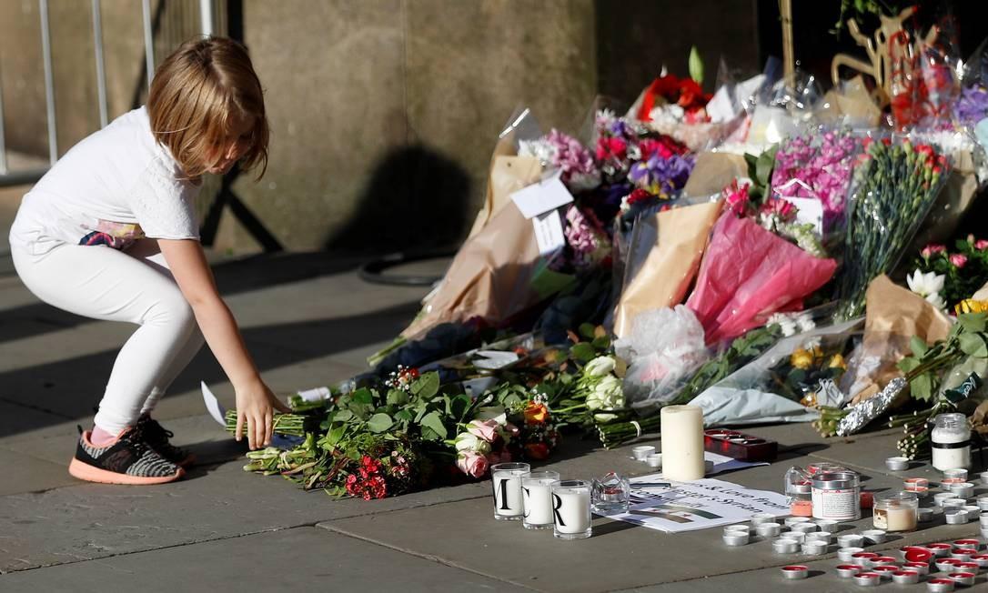 Menina deixa flores para as vítimas do atentado na Arena Manchester Foto: PETER NICHOLLS / REUTERS