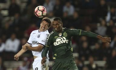 Luiz Otávio disputa jogada pelo alto contra o Lanús: Chapecoense foi punida pela escalação do zagueiro Foto: Agustin Marcarian / AP