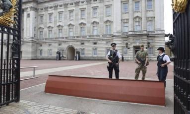 Soldado e policiais fazem segurança da entrada do Palácio de Buckingham, em Londres Foto: Philip Toscano / AP