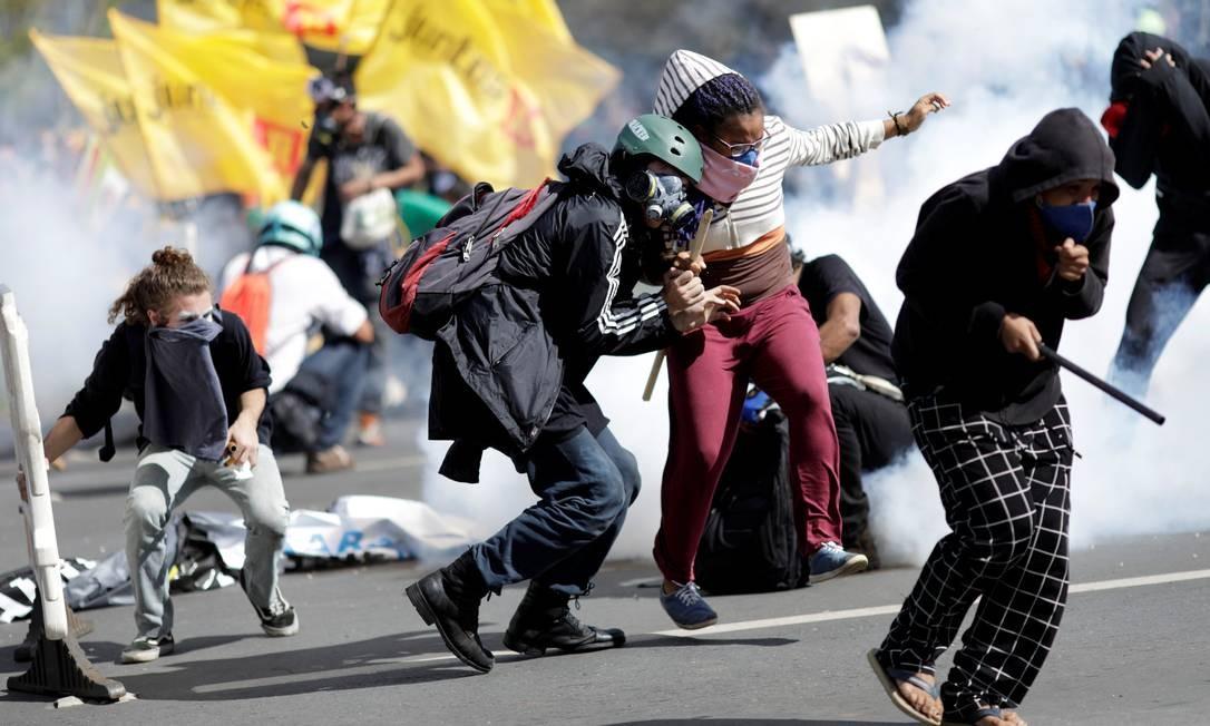Manifestantes tentam se proteger das bombas de efeito moral lançadas pela polícia Foto: Ueslei Marcelino / Reuters