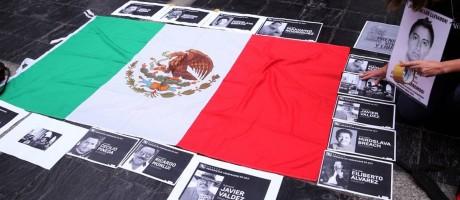 Manifestantes exibem fotos de jornalistas assassinados no México ao lado de bandeira Foto: MARCOS BRINDICCI / REUTERS