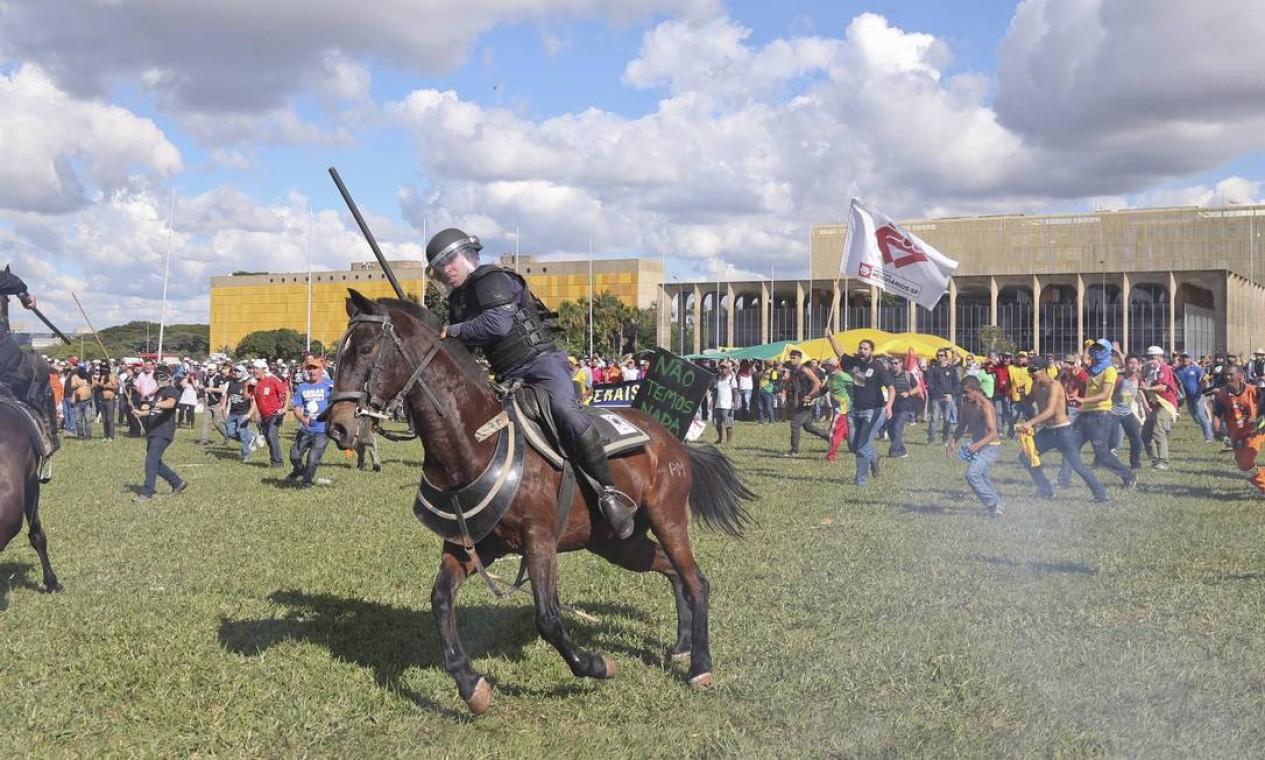 Policiais montados em cavalos são cercados por manifestantes em Brasília Foto: Andre Coelho / O Globo