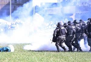 Tropa policial avança enquanto manifestante fica caído no gramado Foto: Jorge William / O Globo