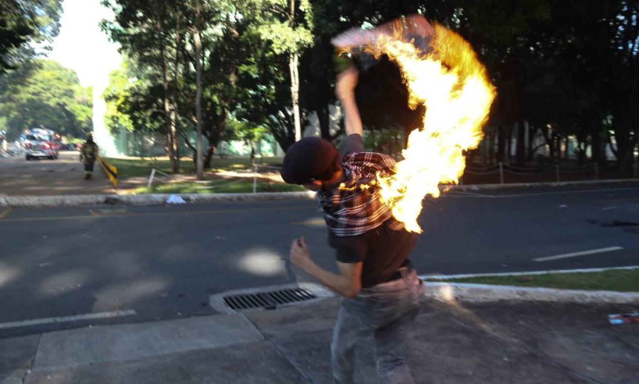 Manifestante arremessa coquetel molotov durante protesto contra o governo Temer em Brasília Foto: Andre Coelho / O Globo