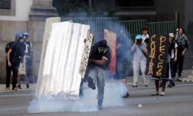 Manifestante se protege de bomba lançada por policiais durante manifestação em frente à Alerj Foto: Marcelo Theobald / Agência O Globo