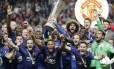 O capitão do Wayne Rooney levanta a taça da Liga Europa cercado pelo time do Manchester United Foto: Michael Sohn / AP