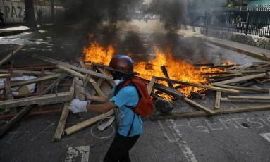 Um manifestante passa em frente a uma barricada durante uma manifestação contra o presidente venezuelano, Nicolás Maduro, em Caracas Foto: CARLOS BARRIA / REUTERS