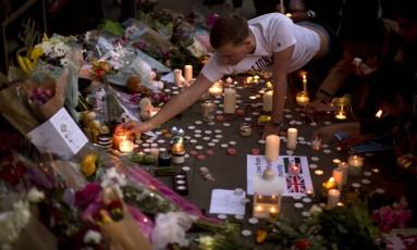 Fãs prestam tributo aos mortos no show de Ariana Grande na Albert Square, em Manchester Foto: Emilio Morenatti / AP