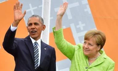 O ex-presidente dos EUA Barack Obama e a chanceler alemã, Angela Merkel, acenam para o público durante um evento no Brandenburg Gate, em Berlim Foto: JOHN MACDOUGALL / AFP