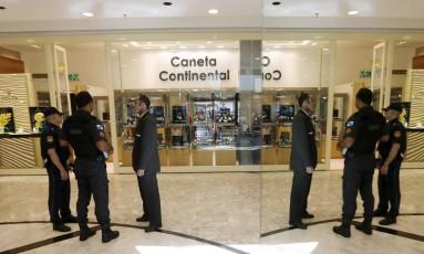 Policiais em frente à loja Caneta Continental, que vende relógios da marca Rolex, no primeiro piso do BarraShopping Foto: Antonio Scorza / Agência O Globo