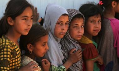 Crianças fazem fila para receber alimentos em campo para deslocados ao sul de Mossul, no Iraque Foto: AHMAD AL-RUBAYE / AFP