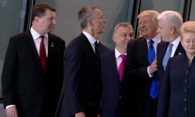 O primeiro-ministro de Montenegro, Dusko Markovic, aparece sendo empurrado pelo presidente dos Estados Unidos, Donald Trump, em um encontro de inauguração da nova sede da Otan, em Bruxelas Foto: AP