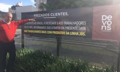 Augusto Santos, proprietário da Denvos, e a faixa avisando sobre o boicote Foto: Reprodução Facebook