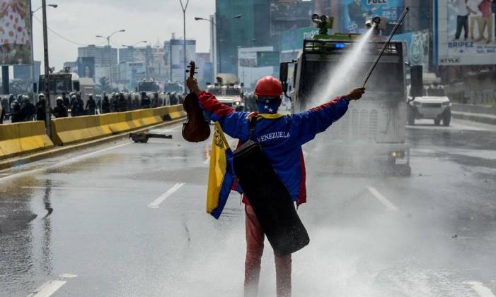 Violinista venezuelano segura seu violino enquanto enfrenta os jatos d'água em um protesto contra o presidente Nicolás Maduro Foto: FEDERICO PARRA / AFP