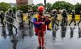 Wuilly Arteaga, 23 anos, toca seu violino enquanto forças de segurança venezuelana passam atrás, em uma das manifestações contra o presidente Nicolás Maduro Foto: FEDERICO PARRA / AFP