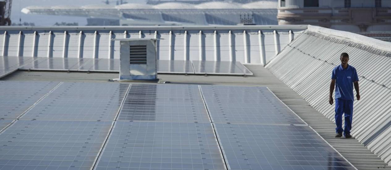 Meio ambiente. Funcionário caminha junto às placas solares instaladas no AquaRio: sistema reduz emissão de gases Foto: Fernando Lemos / Agência O Globo