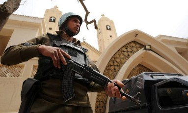 Policial armado faz patrulha em frente a igreja copta bombardeada em abril no Egito Foto: Mohamed Abd El Ghany / REUTERS