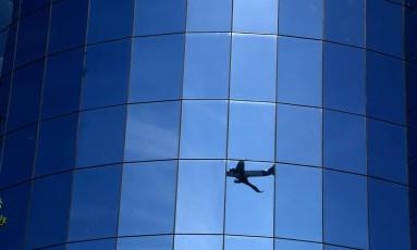 O reflexo de um avião e do céu azul num prédio envidraçado Foto: Custódio Coimbra / Agência O Globo