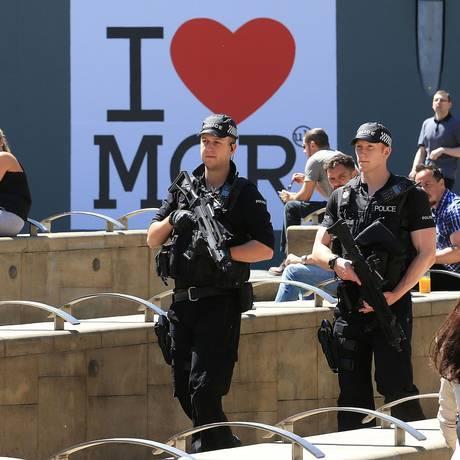 Policiais armados passam em frente ao símbolo de Manchester enquanto fazem patrulha na cidade, após ataque que deixou 22 mortos Foto: LINDSEY PARNABY / AFP